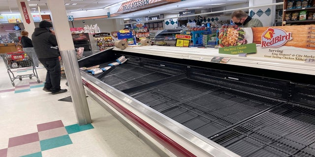 The refrigerated case for packages of chicken is almost empty as a shopper passes by late Thursday in a grocery store in south Denver. Grocers have been overrun by shoppers as they prepare to possibly be homebound for several days as a major storm targets the intermountain West. (AP)