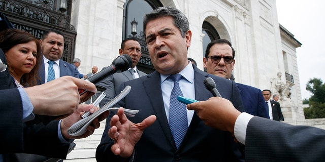 Honduran President Juan Orlando Hernandez speaks to reporters as he leaves a meeting at the Organization of American States, in Washington on Aug. 13, 2019. (AP Photo/Jacquelyn Martin, File)