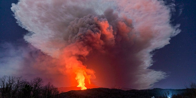 FILE - In this Wednesday, Feb. 24, 2021 file photo, a fiery river of glowing lava flows on the north-east side of the Mt. Etna volcano engulfed with ashes and smoke near Milo, Sicily.  (AP Photo/Salvatore Allegra, File )