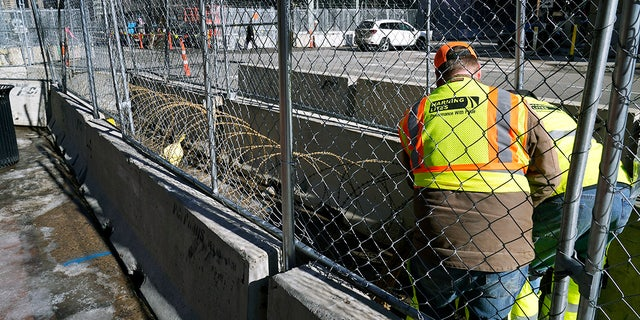 Workers install concertina wire between fenced barriers outside the Hennepin County Government Center, Wednesday, Feb. 23, 2021 in Minneapolis, as part of security in preparation for the trial of former Minneapolis police officer Derek Chauvin.  (AP Photo/Jim Mone)