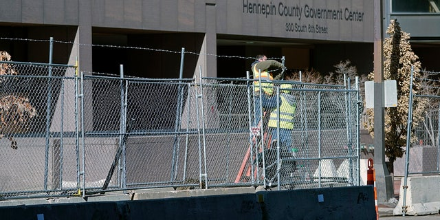 Workers install barbed wire on fencing outside the Hennepin County Government Center, Wednesday, Feb. 23, 2021 in Minneapolis, as part of security preparation for the trial of former Minneapolis police officer Derek Chauvin.  (AP Photo/Jim Mone)