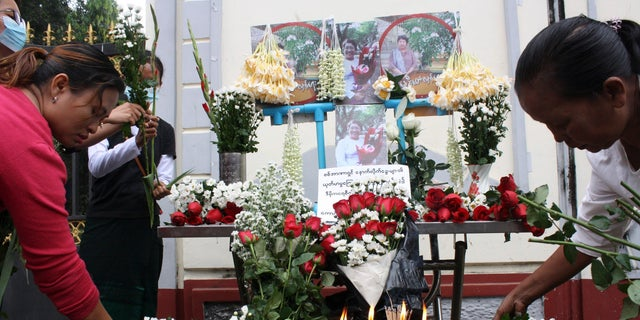 People offer flowers as a tribute to a teacher who died in a protest on Feb 28, during a memorial service in Yangon, Burma, Monday, March 1, 2021. (AP Photo)