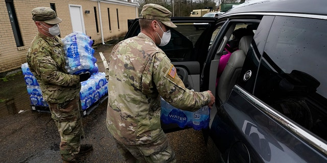 Mississippi Army National Guard Sgt. Chase Toussaint, right, and Staff Sgt. Matthew Riley, both with the Maneuver Area Training Equipment Site of Camp Shelby, place bottled water into a vehicle, Monday, March 1, 2021, in Jackson, Miss. (Associated Press)