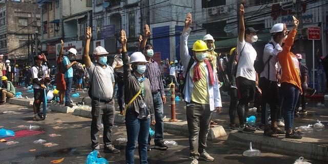 सुरक्षा हेल्मेट पहने हुए प्रदर्शनकारियों ने यांगून, बर्मा में मंगलवार, 2 मार्च, 2021 को एक अवरुद्ध सड़क पर एक बाधा के पीछे एक तख्तापलट के विरोध के दौरान नारे लगाए और तीन-उंगली सलामी दी।