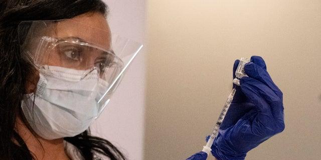 A nurse loads a syringe with the Johnson & Johnson COVID-19 vaccine at a New York hospital (AP Photo/Mark Lennihan)