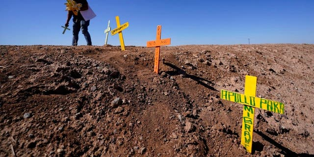 Hugo Castro leaves crosses at the scene of a deadly crash in Holtville, Calif., Tuesday, March 2, 2021. Authorities say a semitruck crashed into an SUV, killing multiple people. (AP Photo/Gregory Bull)