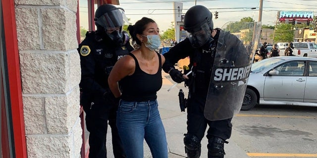 Police officers are shown arresting Des Moines Register reporter Andrea Sahouri after a Black Lives Matter protest she was covering on May 31, 2020, in Des Moines, Iowa, was dispersed by tear gas.(Photo courtesy Katie Akin via AP)