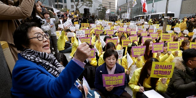"""FILE - In this March 1, 2017, file photo, former """"comfort woman"""" Lee Yong-soo, left, who was forced to serve for the Japanese troops as a sex slave during World War II, shouts slogans during a rally to mark the March First Independence Movement Day, the anniversary of the 1919 uprising against Japanese colonial rule, near the Japanese Embassy in Seoul, South Korea. Harvard University law professor J. Mark Ramseyer alleged in a December 2020 article, scheduled to appear in the March 2021 issue of the International Review of Law and Economics, that the Korean women had actually chosen to work as prostitutes. Lee described Ramseyer's claim as """"ludicrous"""" and demanded an apology. (AP Photo/Ahn Young-joon, File)"""