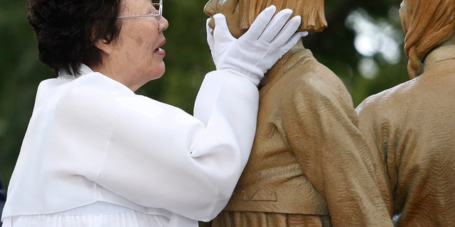 """FILE - In this Aug. 14, 2019, file photo, Lee Yong-soo, who was forced to serve for the Japanese troops as a sex slave during World War II, touches the face of a statue of a girl symbolizing the issue of wartime """"comfort women"""" during its unveiling ceremony in Seoul, South Korea. Harvard University law professor J. Mark Ramseyer alleged in a December 2020 article, scheduled to appear in the March 2021 issue of the International Review of Law and Economics, that the Korean women had actually chosen to work as prostitutes. Lee described Ramseyer's claim as """"ludicrous"""" and demanded an apology. (AP Photo/Ahn Young-joon, File)"""