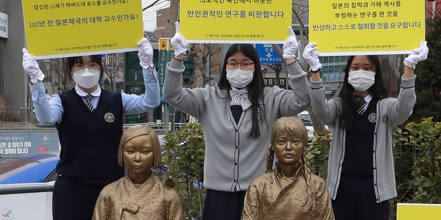"""In this Feb. 25, 2021, photo, high school students hold up banners to protest a recent academic paper by Harvard University professor J. Mark Ramseyer, behind statues symbolizing wartime sex slaves in Seoul, South Korea. The signs read: """"J. Mark Ramseyer, are you a 21st century professor at Harvard? Are you a university professor in the Japanese Empire 100 years ago? We criticize anti-human rights research."""" (Lee Jung-hoon/Yonhap via AP)"""