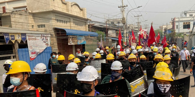 Protesters march with makeshift shields on a main road during a demonstration in Mandalay, Burma, Monday, March 8, 2021. Large protests have occurred daily across many cities and towns in Burma. (AP Photo)