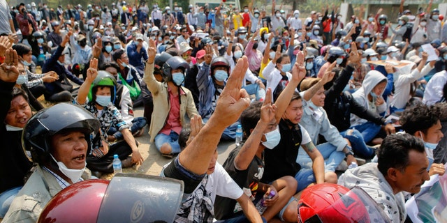 Anti-coup protesters flash a three-fingered sign of resistance during a demonstration in Naypyitaw, Burma, Monday, March 8, 2021. The escalation of violence in Burma as authorities crackdown on protests against the Feb. 1 coup is raising pressure for more sanctions against the junta, even as countries struggle over how to best sway military leaders inured to global condemnation. (AP Photo)
