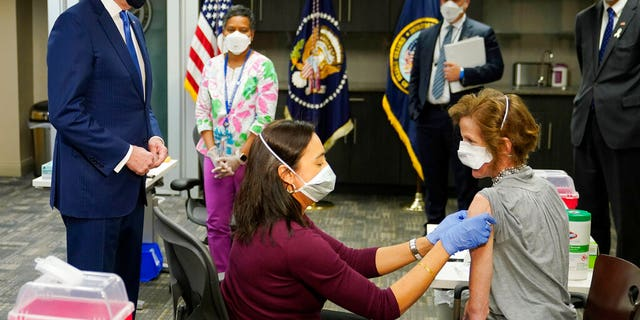 President Joe Biden, standing left, visits a COVID-19 vaccination site and watches as Dr. Navjit Goraya administers a vaccine to the Air Force Colonel.