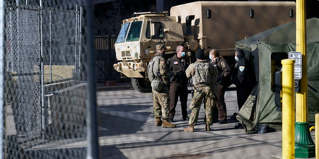 Deputies and National Guard soldiers converse, Tuesday, March 9, 2021, in Minneapolis where the trial for former Minneapolis police officer Derek Chauvin continues with jury selection. Chauvin is charged with murder in the death of George Floyd during an arrest last may in Minneapolis. AP Photo/Jim Mone)