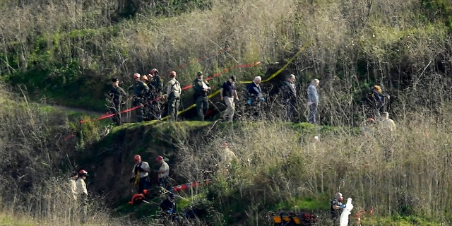 In this Jan. 27, 2020, file photo, investigators work the scene of a helicopter crash that killed former NBA basketball player Kobe Bryant in Calabasas, Calif. (AP Photo/Mark J. Terrill, File)