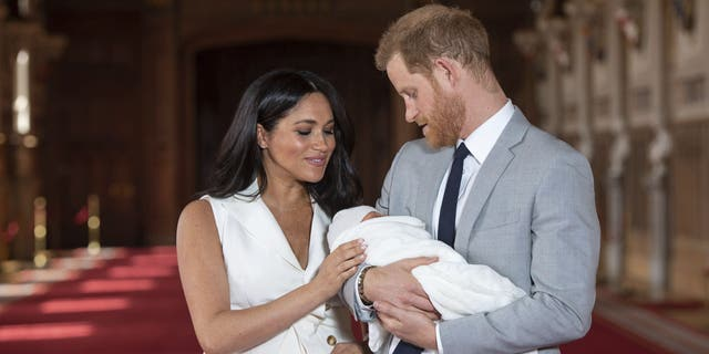 FILE - In this Wednesday May 8, 2019 file photo, Britain's Prince Harry and Meghan, Duchess of Sussex, pose during a photocall with their newborn son Archie, in St George's Hall at Windsor Castle, Windsor, south England. One of the most dramatic claims in Prince Harry and Meghan's interview with Oprah Winfrey was that their son was denied a royal title, possibly because of the color of his skin. Queen Elizabeth II has nine great-grandchildren, including Archie. They are not princes and princesses, apart from the three children of Prince William, who is second in line to the throne and destined to be king one day. (Dominic Lipinski/Pool via AP, File)
