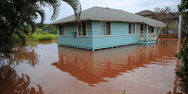 A house on Haleiwa Road is surrounded by floodwaters Tuesday, March 9, 2021, in Haleiwa, Hawaii. Torrential rains have inundated parts of Hawaii for the past several days. (Jamm Aquino/Honolulu Star-Advertiser via AP)