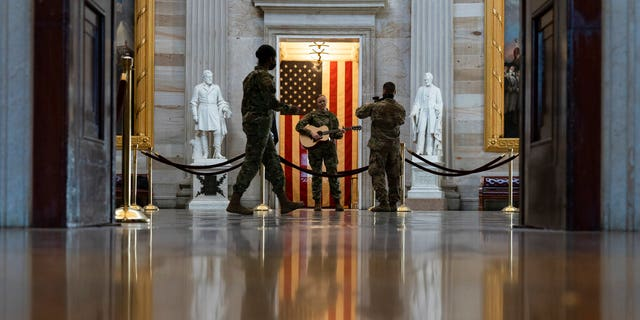 U.S. Army Michigan National Guard Sgt. Hannah Boulden, from Ann Arbor, Mich., plays her guitar and sings in the Rotunda of the U.S. Capitol, before the vote on the Democrat's $1.9 trillion COVID-19 relief bill, on Capitol Hill, Wednesday, March 10, 2021, in Washington. (AP Photo/Alex Brandon)
