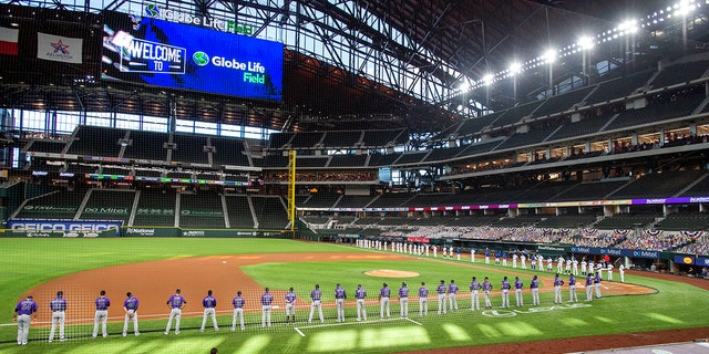 File-On Friday, July 24, 2020, before the first day of baseball in Arlington, Texas, the Texas Rangers and the Colorado Rockies lined up on the Globe Life Field foul line.  (AP Photo/Jeffrey McWalter, file)