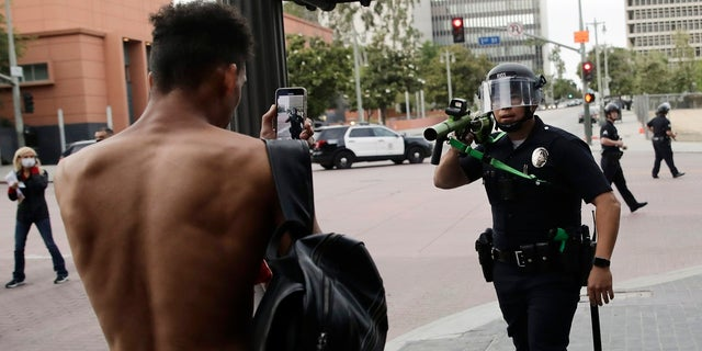 FILE - In this June 2, 2020, file photo, a police officer aims his less-lethal weapon at a demonstrator during a protest in Los Angeles, over the death of George Floyd on May 25 while in police custody in Minneapolis. (AP Photo/Jae C. Hong, File)