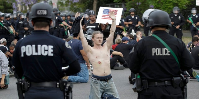 FILE - In this June 1, 2020, file photo, a protester raises his arm shortly before being arrested for violating a curfew in the Hollywood area of Los Angeles during demonstrations over the death of George Floyd. (AP Photo/Marcio Jose Sanchez, File)