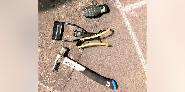 This photo released by Portland Police Bureau shows numerous items left behind by people inside the perimeter of a march, including, high impact slingshot, and knives, after they corralled a group of about 100 hundred protesters Friday night in Portland, Ore. (Portland Police Department via AP)