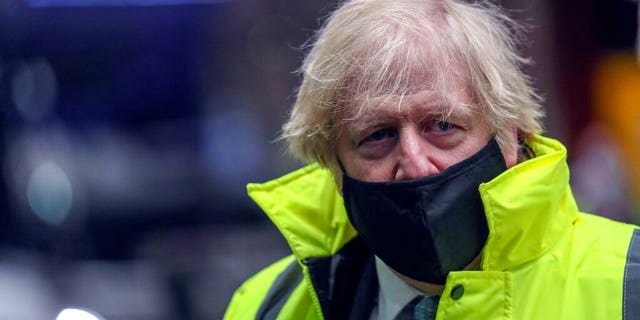 Britain's Prime Minister Boris Johnson visits the National Express depot in Coventry, central England, Monday March 15, 2021.