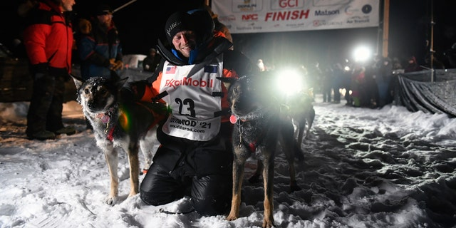 Dallas Seavey poses with his dogs after crossing the finish line to win the Iditarod Trail Sled Dog Race race near Willow, Alaska, early Monday, March 15, 2021. (Marc Lester/Anchorage Daily News via AP, Pool)