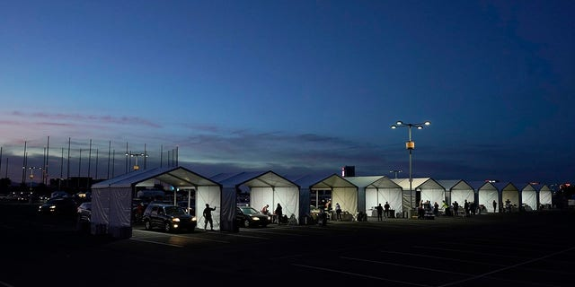 In this Jan. 12, 2021, file photo, several tents are set up so people who have registered can get their COVID-19 vaccinations as they drive-thru the parking lot of the State Farm Stadium in Glendale, Arizona. (AP Photo/Ross D. Franklin)