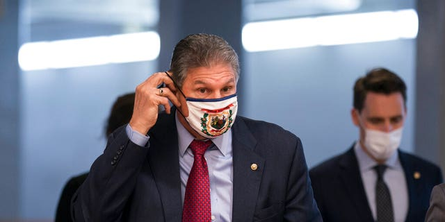 Sen. Joe Manchin, D-W.Va., adjusts his face mask as he arrives for votes on Biden administration nominees, at the Capitol in Washington, Tuesday, March 16, 2021.