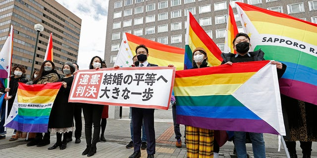 """Plaintiffs' lawyers and supporters hold rainbow flags and a banner that reads: """"Unconstitutional judgment"""" outside Sapporo District Court after a court rule, in Sapporo, northern Japan, Wednesday, March 17, 2021. The court ruled the government's ban on same-sex marriages is unconstitutional, recognizing the rights of same-sex couples for the first time in the only Group of Seven country that doesn't acknowledge their legal partnership. (Yohei Fukai/Kyodo News via AP)"""