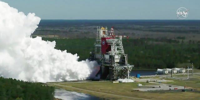 In this image from video made available by NASA, the core stage of the Space Launch System, NASA's planned moon rocket, is tested at the Stennis Space Center near Bay St. Louis, Miss., on Thursday, Mar. 18, 2021.
