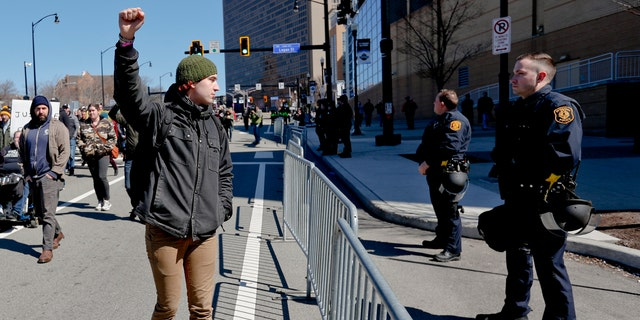 In this March 23, 2019, file photo, a marcher holds up his fist while staring at police lined up in front of PPG Paints Arena in Pittsburgh during a protest after a former suburban police officer was acquitted of a homicide charge in the on-duty shooting death of Antwon Rose II in East Pittsburgh. (AP Photo/Keith Srakocic)