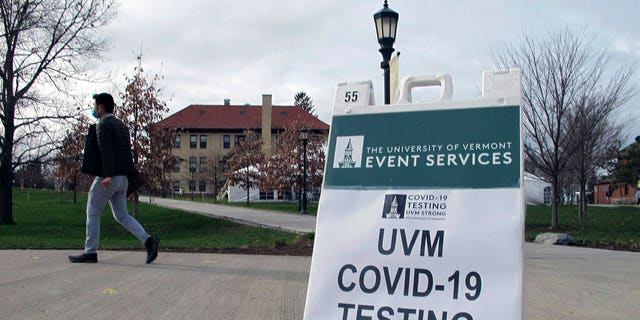 FILE: A University of Vermont student walks toward a tent leading to a COVID-testing site on campus in Burlington, Vt.