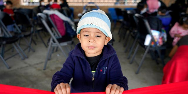 Santiago Lopez Paz, 3, a migrant from Honduras, stands in a respite center hosted by a humanitarian group after he and his family were released from U.S. Customs and Border Protection custody, Saturday, March 20, 2021, in Brownsville, Texas. (AP Photo/Julio Cortez)