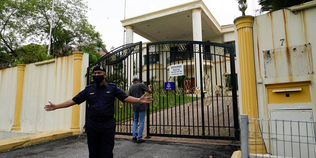 A staff locks the front gate of North Korean embassy in Kuala Lumpur, on Sunday. Malaysia on Friday ordered all North Korean diplomats to leave the country within 48 hours, an escalation of a diplomatic spat over Malaysia's move to extradite a North Korean suspect to the United States on money laundering charges. (AP Photo/Vincent Thian)