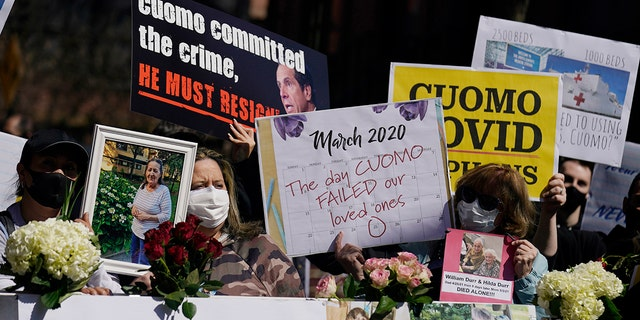 Families who had relatives die from COVID-19 in nursing homes hold signs in front of a section of a memorial wall at a news conference in New York, Sunday, March 21, 2021. They gathered to grieve but want an investigation into and accountability from Gov. Andrew Cuomo's handing of nursing homes in New York. (AP Photo/Seth Wenig)