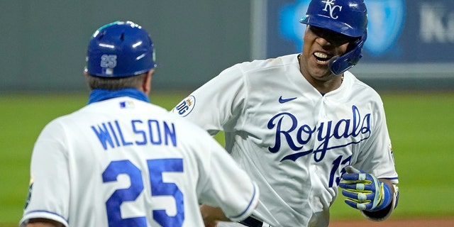 In this Thursday, Sept. 24, 2020 photo, Kansas City Royals' Salvador Perez celebrates with third base coach Vance Wilson after hitting a three-run home run during the first inning of the team's baseball game against the Detroit Tigers in Kansas City, Mo. (AP Photo/Charlie Riedel, File)