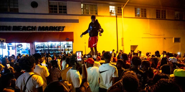 A man stands on a car as crowds defiantly gather in the street while a speaker blasts music an hour past curfew in Miami Beach, Fla., on Sunday, March 21, 2021.