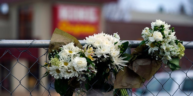 Bouquets line a fence put up around the parking lot where a mass shooting took place the day before in a King Soopers grocery store, Tuesday, March 23, 2021, in Boulder, Colo. (AP Photo/David Zalubowski)
