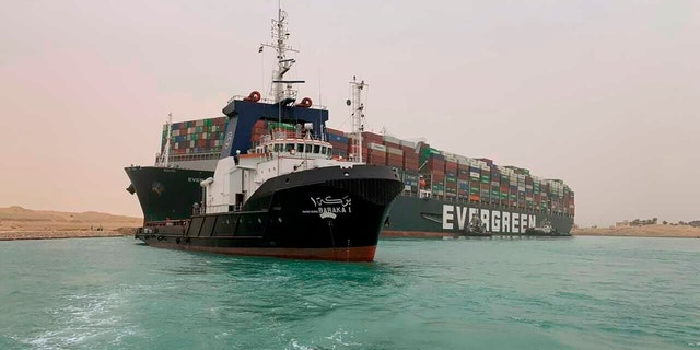 In this photo released by the Suez Canal Authority, a boat navigates in front of a massive cargo ship, named the Ever Green, rear, sits grounded Wednesday, March 24, 2021. (Suez Canal Authority via AP)