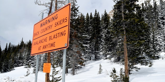 A sign warns backcountry users about avalanche blasting near the Continental Divide near Vail, Colo., Monday, March 22, 2021. Evan Hannibal, of Vail, and Tyler DeWitt, of Silverthorne, were involved in an avalanche in the area last spring that buried a service road and destroyed an expensive avalanche mitigation system. The two are scheduled to go to trial Thursday, March 25, 2021, on charges of misdemeanor reckless endangerment. Prosecutors also are seeking $168,000 in damages in the rare case that some worry could deter other backcountry skiers and snowboarders from coming forward to report avalanches out of fear of costly retribution. (AP Photo/Thomas Peipert)
