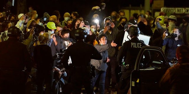 Homeless residents of Echo Park confront Los Angeles Police officers moving in to remove residents in the Echo Park Lake homeless encampment in Los Angeles late Wednesday, March 24, 2021. (Associated Press)