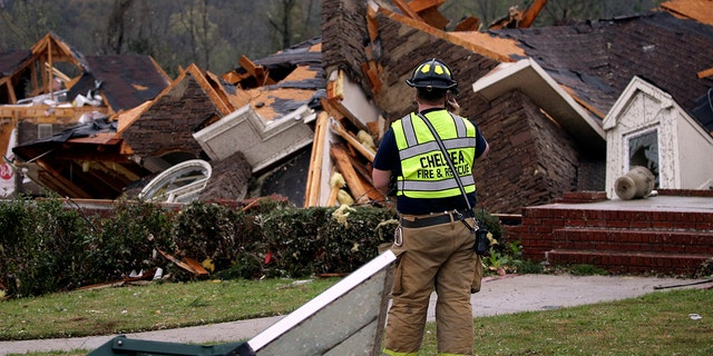 A firefighter surveys damage to a house where the family was trapped, but were able to get out after a tornado touched down south of Birmingham, Ala., March 25, 2021. (Associated Press)