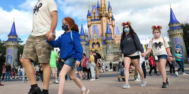 A family walks past Cinderella Castle in the Magic Kingdom, at Walt Disney World in Lake Buena Vista, Fla. (Joe Burbank/Orlando Sentinel via AP, File)