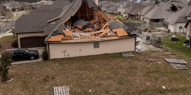 In this image taken with a drone, many homes with damaged roofs, Friday, March 26, 2021, in the Timberline subdivision in Calera, Ala., the day after a severe storm swept through the area. (AP Photo/Vasha Hunt)