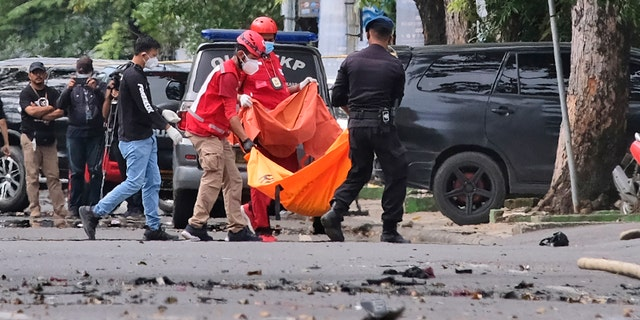 Police officer and rescue workers carry a body bag containing what is believed to be human remains outside a church where an explosion went off in Makassar, South Sulawesi, Indonesia, Sunday, March 28, 2021. A suicide bomber blew himself up outside a packed Roman Catholic cathedral on Indonesia's Sulawesi island during a Palm Sunday Mass, wounding a number of people, police said. (AP Photo/Masyudi S. Firmansyah)
