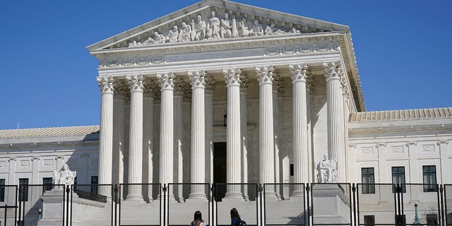 FILE - In this March 21, 2021, file photo people view the Supreme Court building from behind security fencing on Capitol Hill in Washington after portions of an outer perimeter of fencing were removed overnight to allow public access. (AP Photo/Patrick Semansky, File)