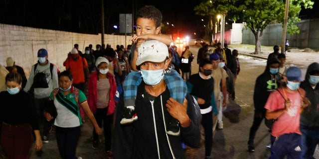 Migrants who aim to reach the U.S. walk along a highway as they leave San Pedro Sula, Honduras before dawn Tuesday. (AP Photo/Delmer Martinez)