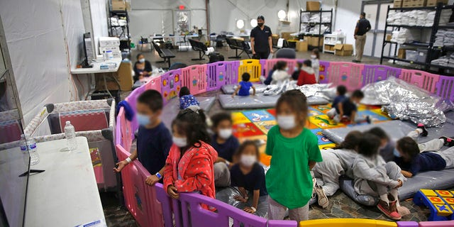 Young unaccompanied migrants, from ages 3 to 9, watch television inside a playpen at the U.S. Customs and Border Protection facility. (AP Photo/Dario Lopez-Mills, Pool)